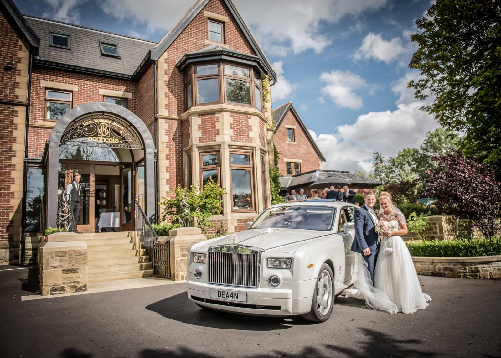 Bride and groom with their wedding car in front of Northcote